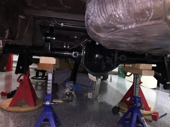 Axle mounted on torsion arms resting on jack stands